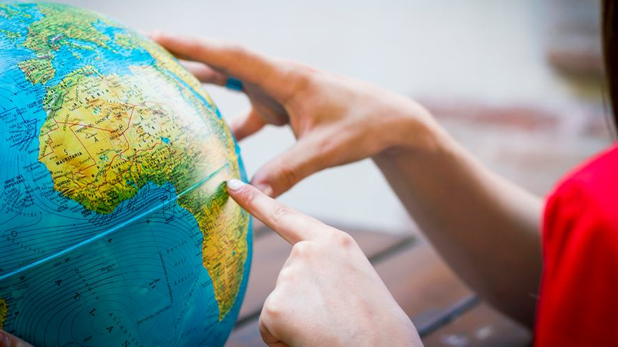 Someone pointing at a globe