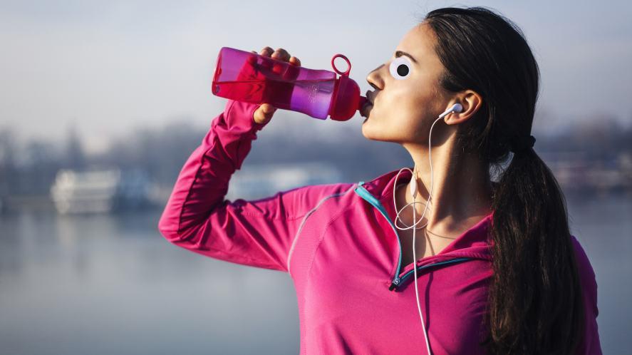 A sporty woman drinking a bottle of water