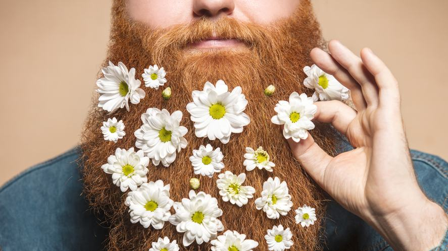 A big bushy beard decorated with daisies