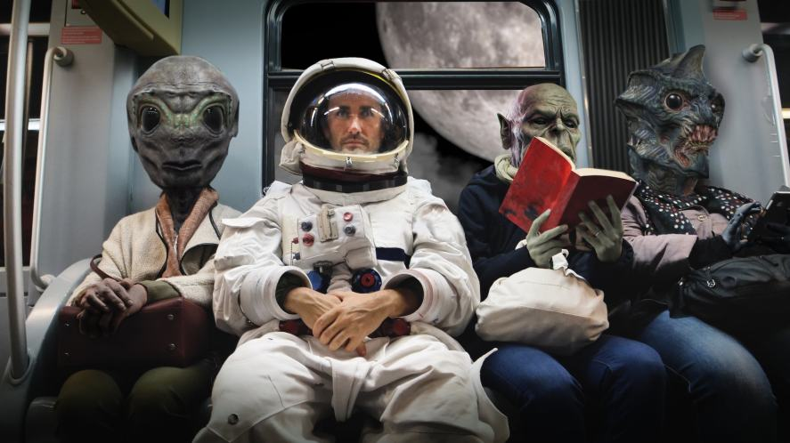 An astronaut and three aliens sitting on a train going to the moon