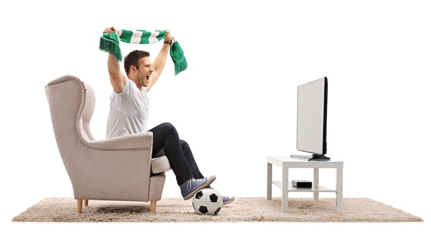 A football fan watching a game from his armchair