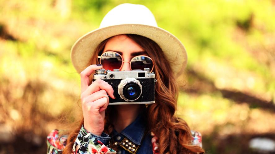 A girl in a hat and sunglasses taking a photograph