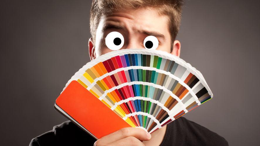 A man peeping behind a colour chart