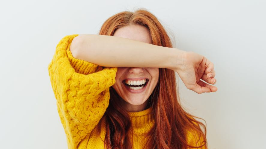 A woman covering her eyes and laughing