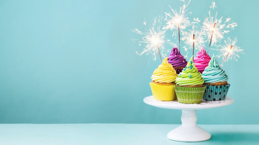 A plate of birthday cupcakes with sparklers