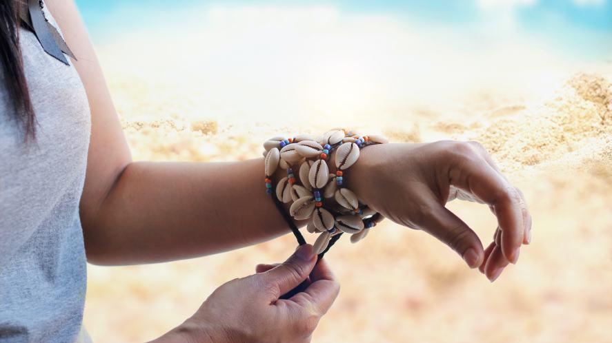 A shell bracelet on a woman's wrist