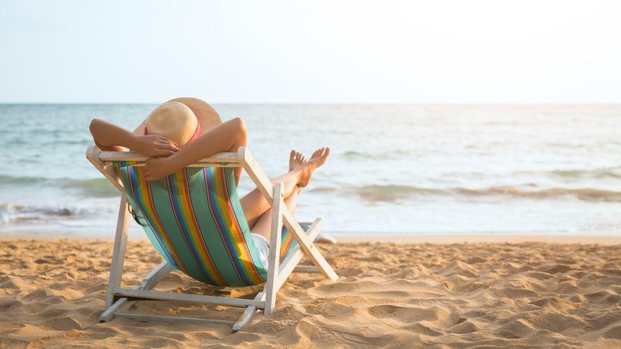 A person relaxing on a deckchair on a sandy beach