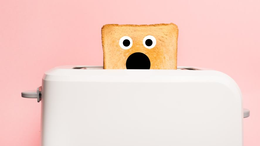 A toaster with a shocked piece of toast popping up