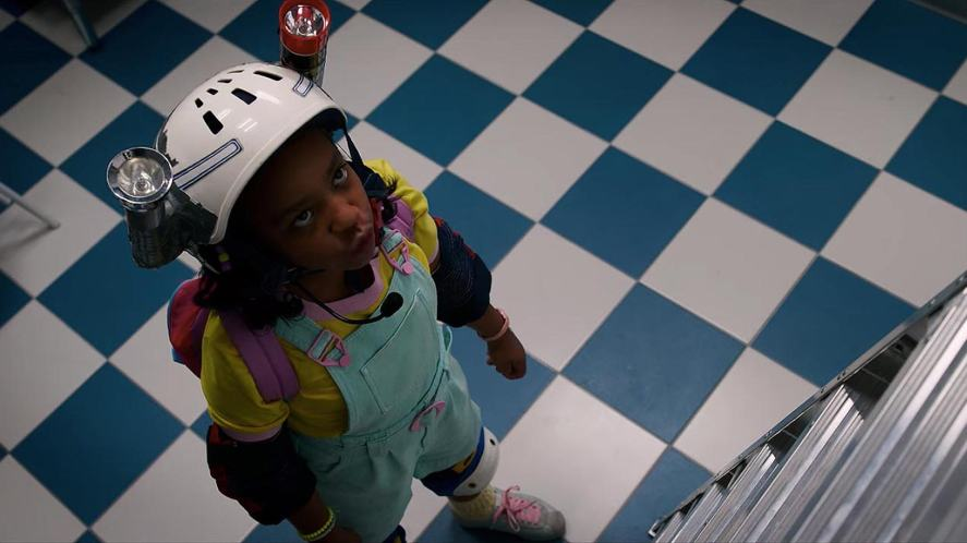 Erica looks up a big ladder in Stranger Things