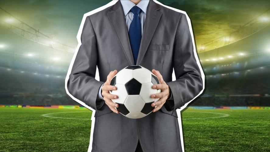 A football manager clutching a ball