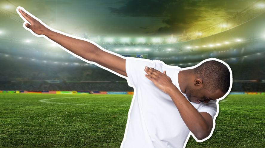 A man dabbing in a football stadium