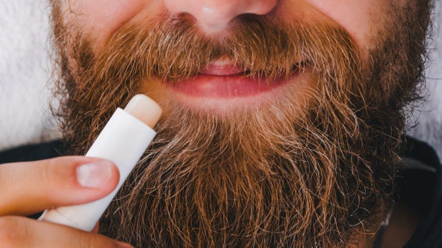 A bearded man putting on some lip balm