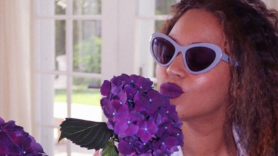 Beyonce smelling a large purple flower
