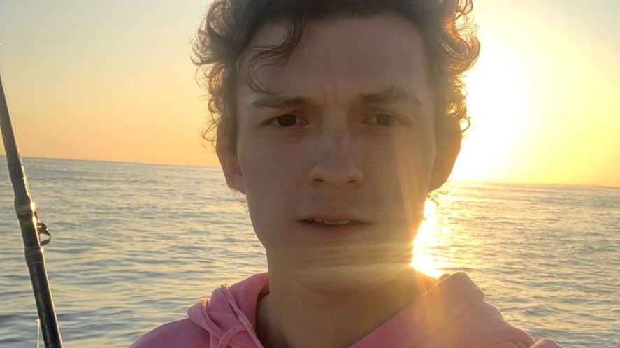 Tom Holland taking a selfie against a sunset