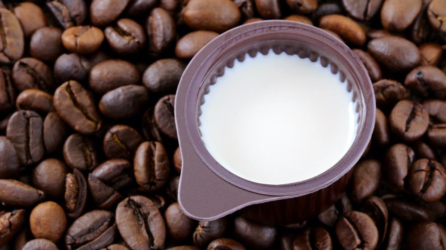 A non-dairy creamer pot in a pile of coffee beans