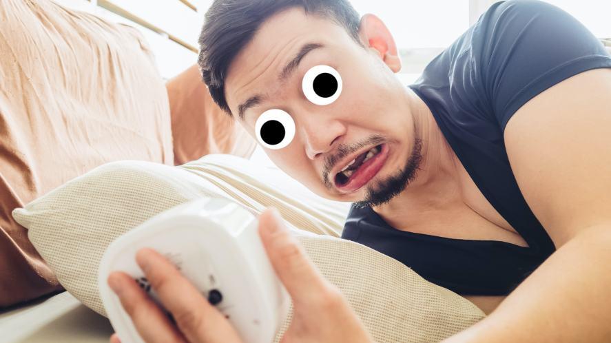 A man waking up late and staring at his alarm clock