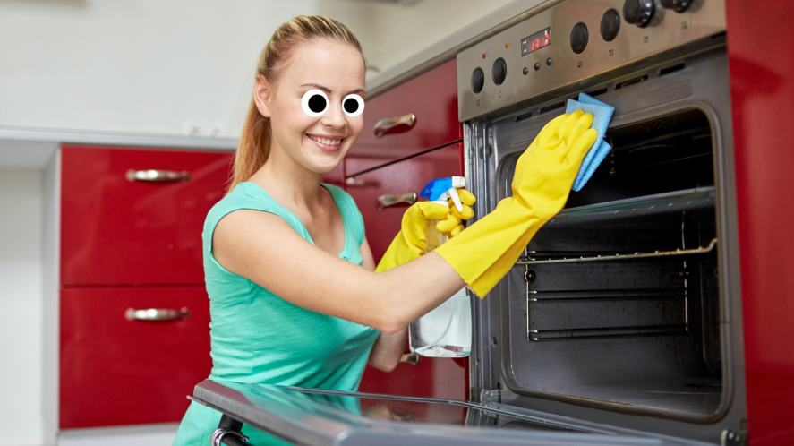 A woman smiling as she cleans an oven