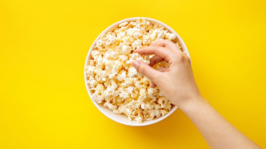 A hand reaching into a tub of popcorn
