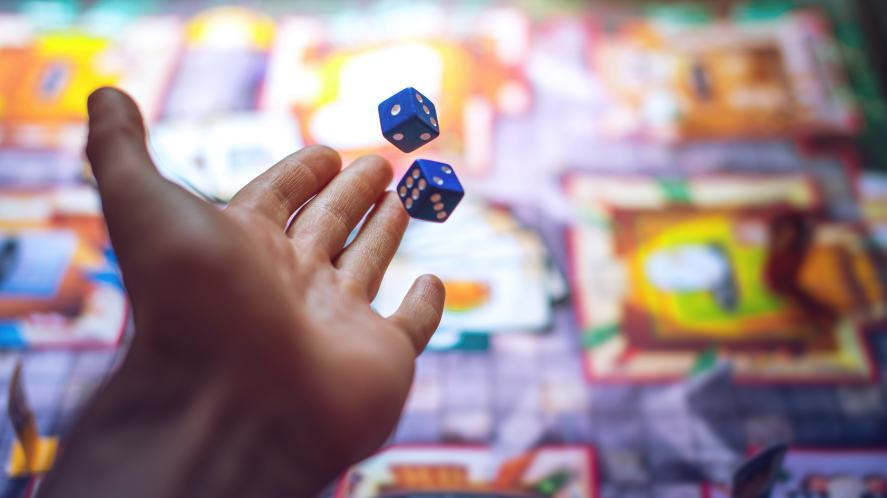 A person rolling the dice while playing a board game