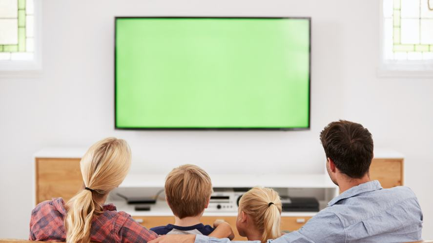 A family watching a green screen on TV