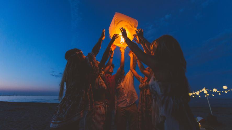 A group of girls lighting a lantern on a beach
