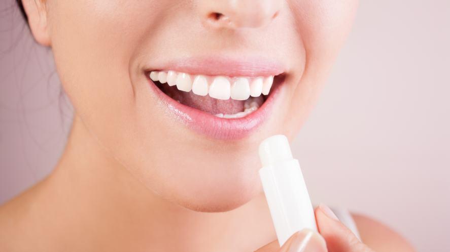 A woman applying lip balm