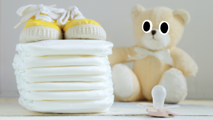 A pile of nappies, baby boots, teddy bear and dummy