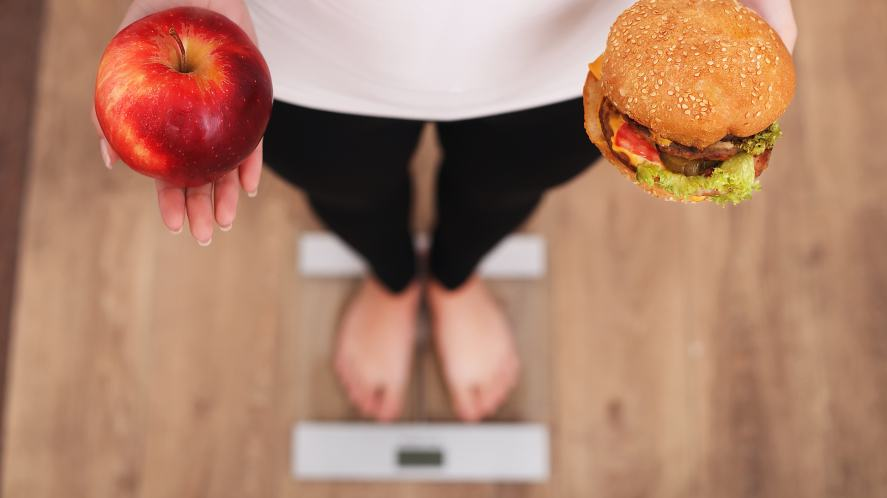 A person holding an apple and a burger on some scales