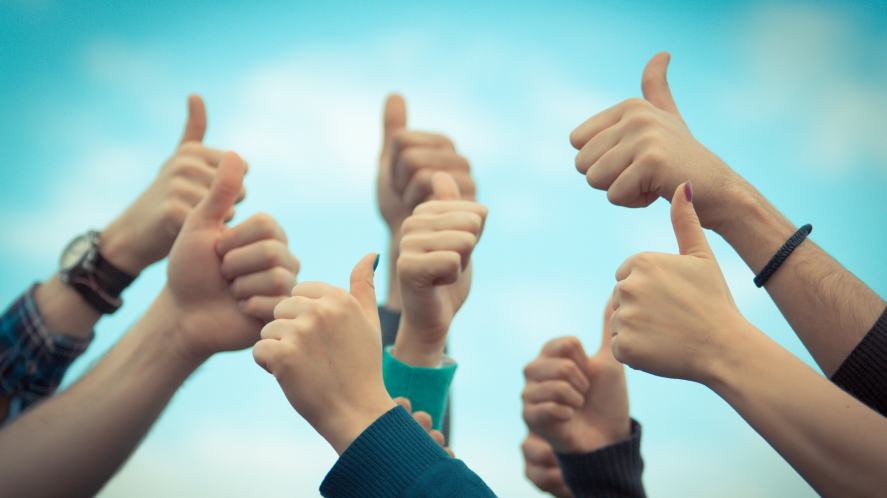 A group of students hold their thumbs up