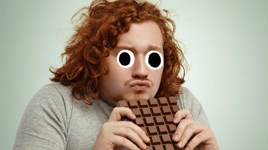A man enjoying a big bar of chocolate