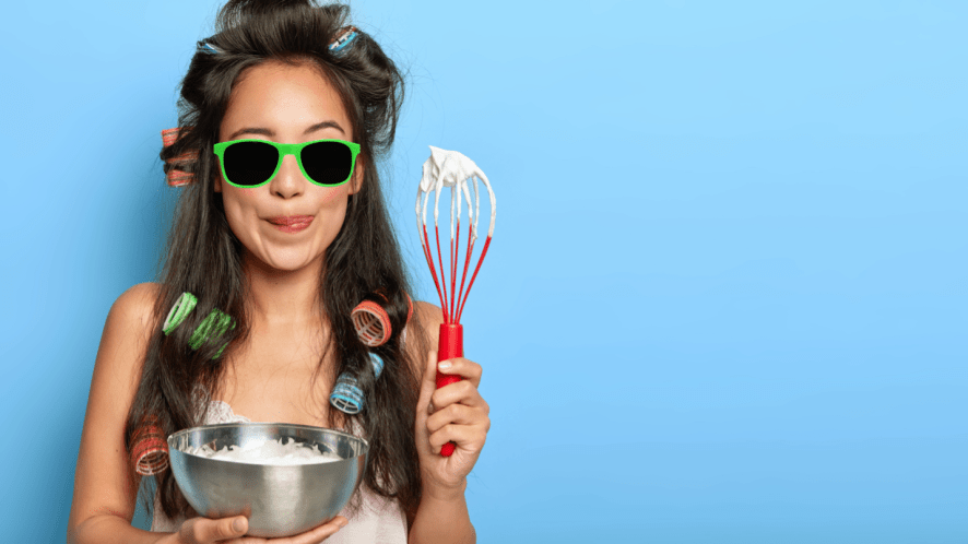 A woman holding a cake bowl and a whisk