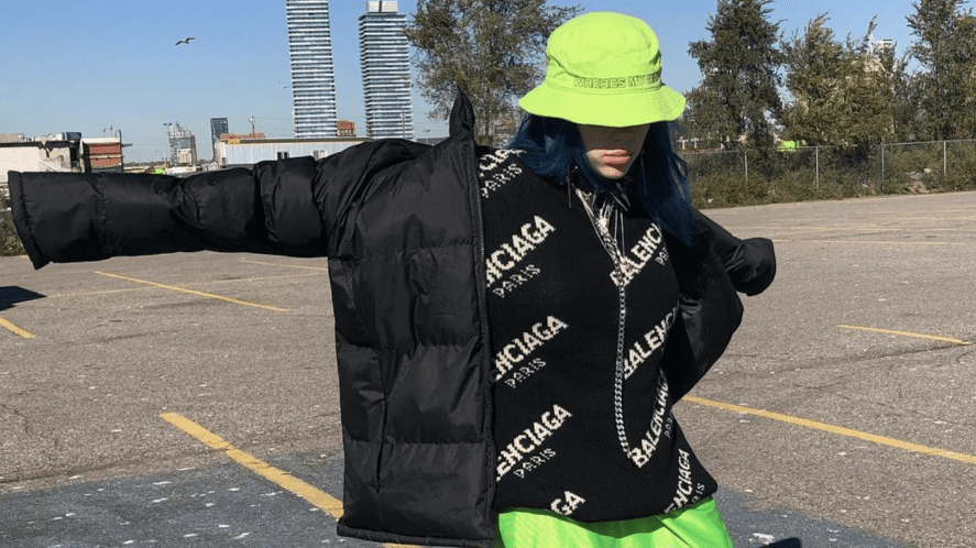 Billie Eilish in a green hat and black coat