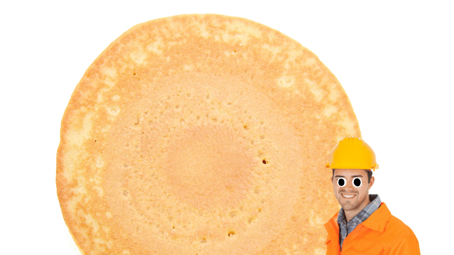 A builder standing next to a huge pancake