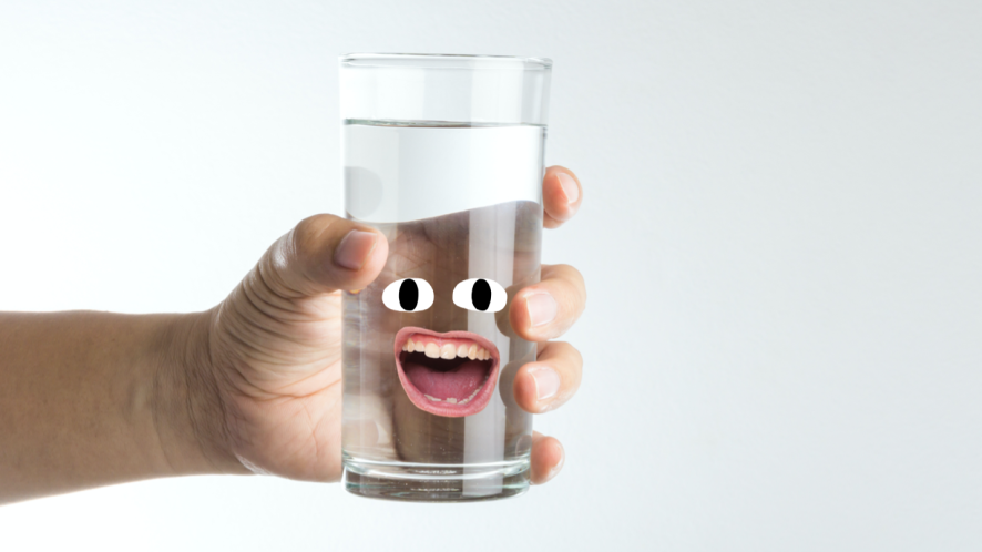 A hand holding a glass of water