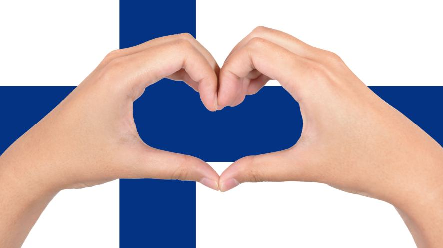 A Finnish flag and a pair of hands making a heart shape