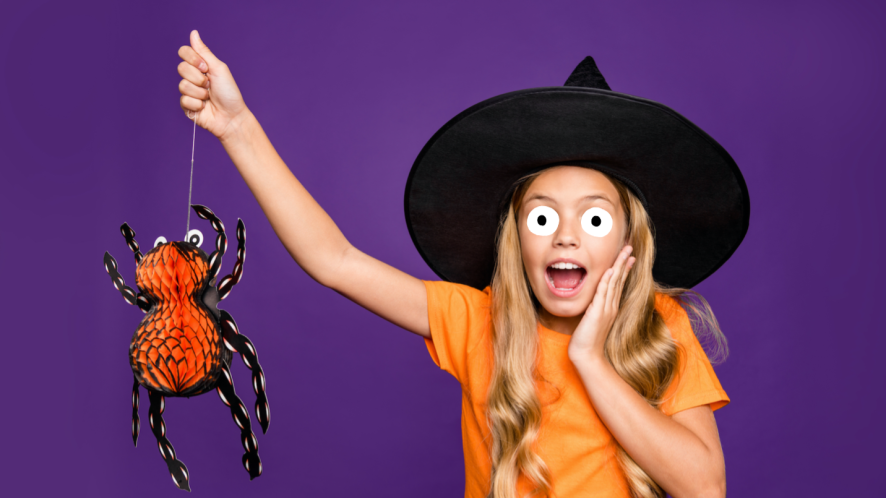 A young witch holding a spider