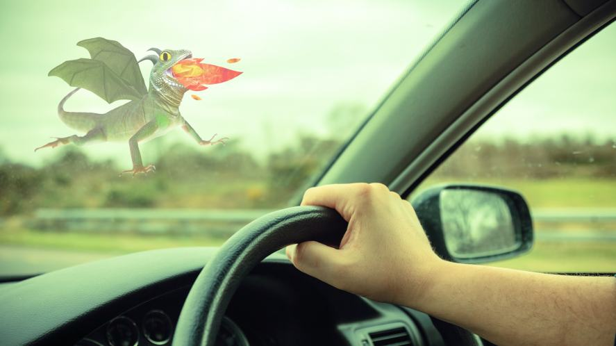 A car dashboard with a dragon in the background