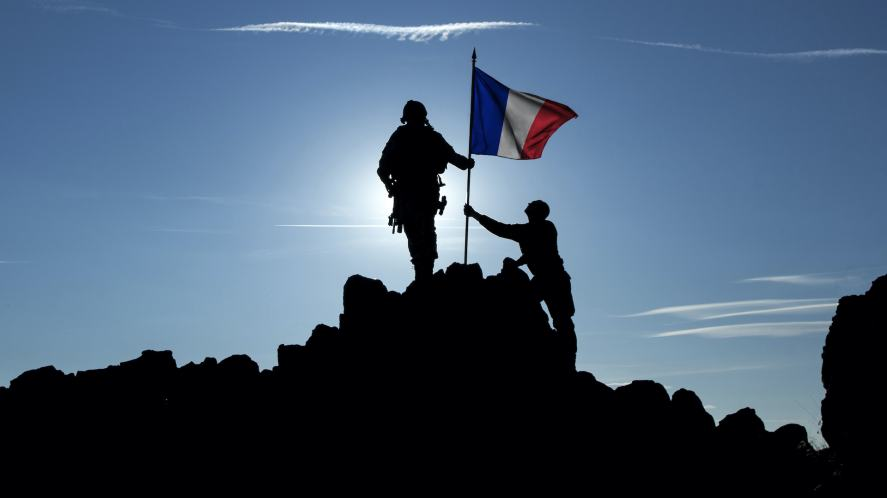 Two people raise the French flag