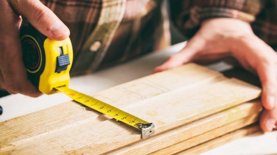A carpenter measuring wood