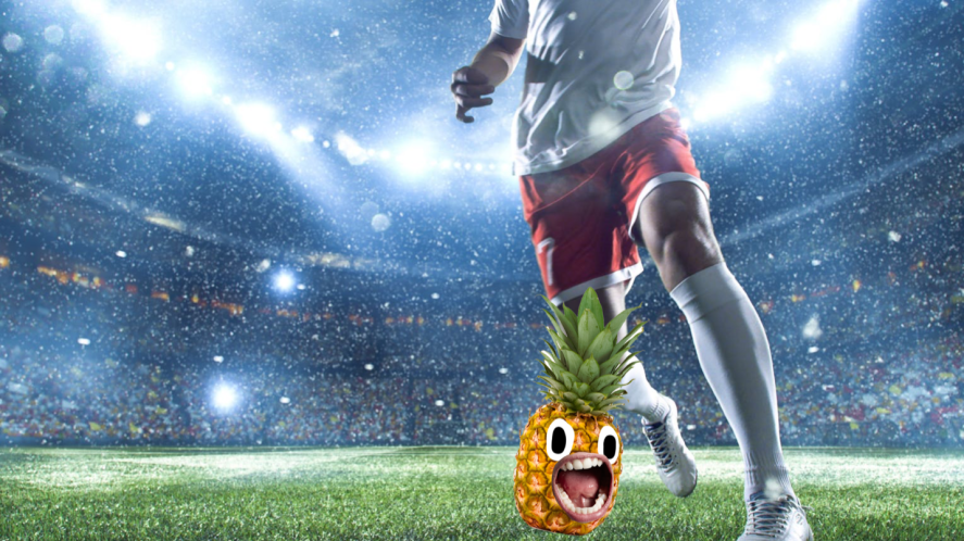 A footballer is about to kick a pineapple