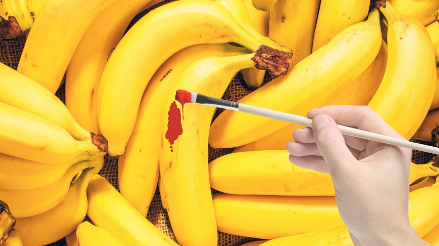 A man painting a banana red