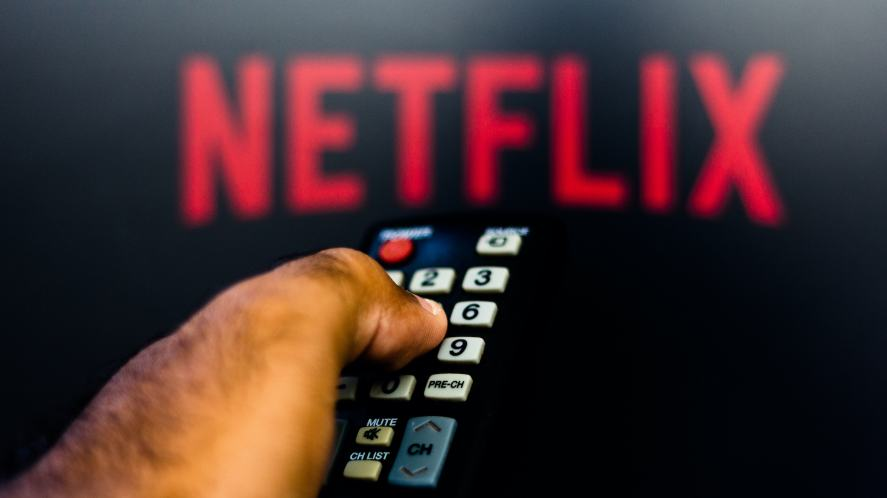 A man holding a remote while watching Netflix