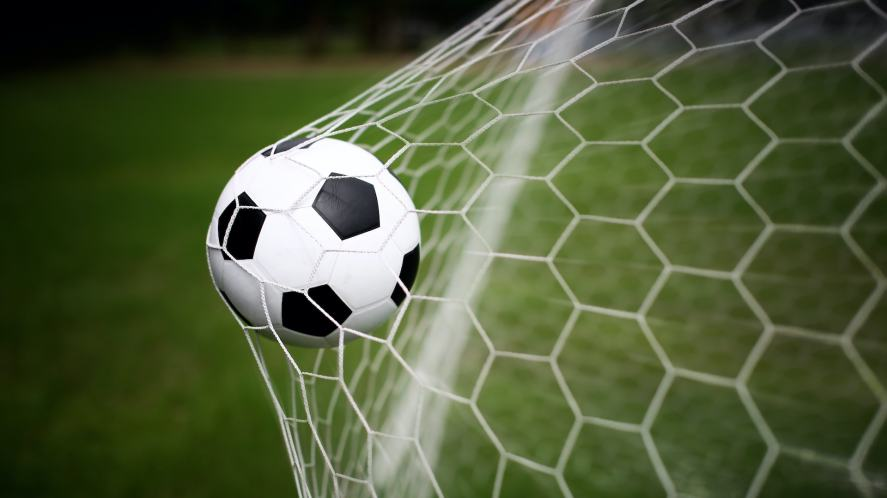 A football hitting the back of the net