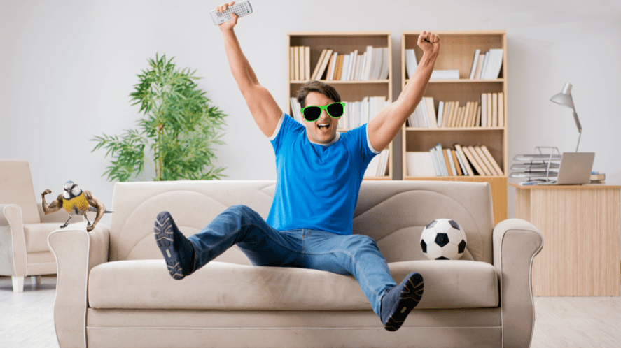 A football fan cheering his team on from a comfy sofa
