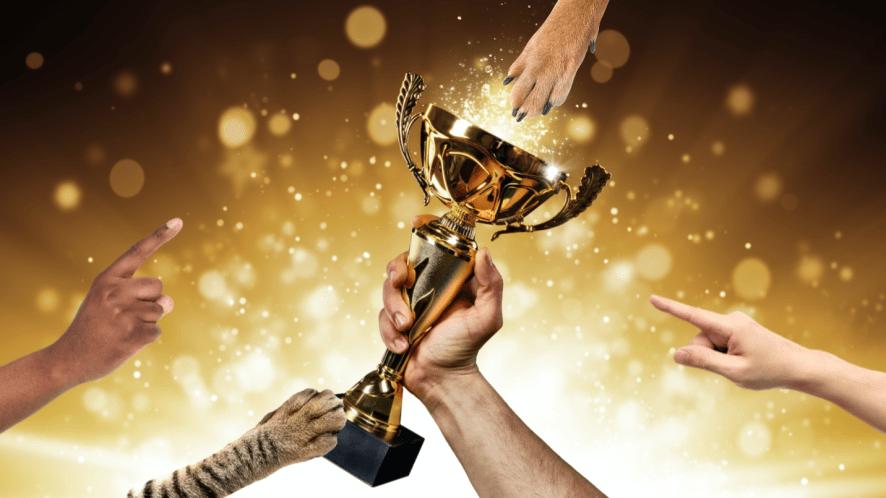 A hand holding a golden trophy