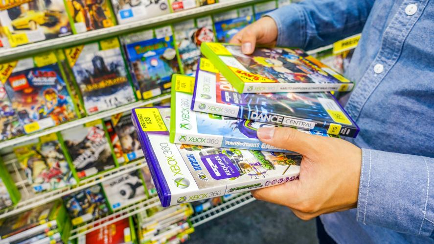 A man holding a selection of pre-owned Xbox games
