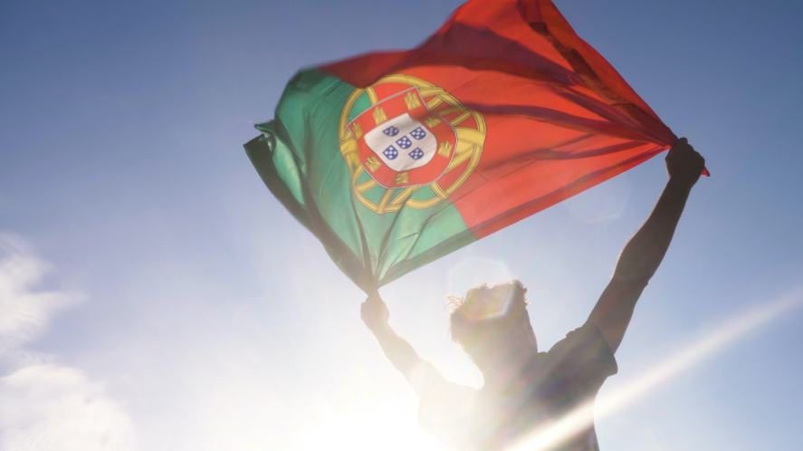A person holding the Portuguese flag aloft in the sunshine