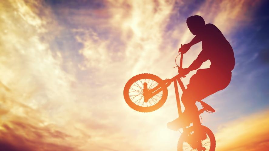 Man riding a BMX bike against the sunset