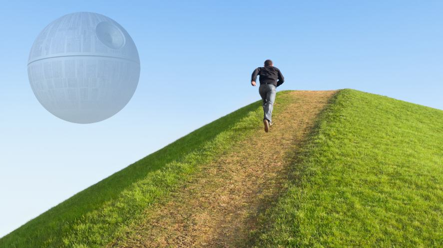 A man climbing a hill with the Death Star in the background