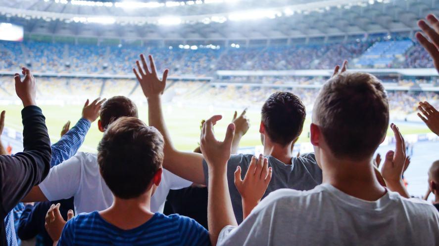 A cheering football crowd in a big stadium